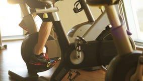 Młody człowiek pracujący na ćwiczenie rowerze w sprawności fizycznej centrum out zbiory