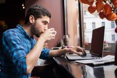młody człowiek pracuje na jego komputerze przy kawiarnią zdjęcie royalty free