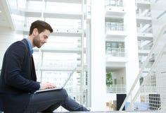 Młody człowiek pracuje na laptopie indoors Obraz Stock