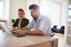 Młody człowiek pracuje na laptopie z kobiety obsiadaniem obok zdjęcie stock