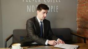Młody człowiek pracuje na laptopu obsiadaniu w kawiarni zamyka jego laptop i iść alonng zbiory wideo
