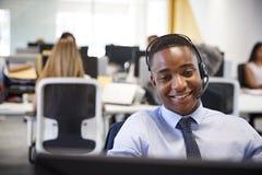 Młody człowiek pracuje przy komputerem z słuchawki w ruchliwie biurze zdjęcia royalty free