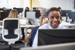 Młody człowiek pracuje przy komputerem z słuchawki w ruchliwie biurze fotografia stock