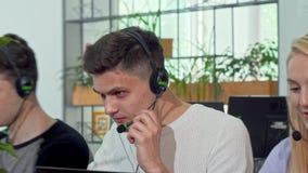 Młody człowiek pracuje przy obsługi klientej centrum telefonicznym, jest ubranym słuchawki zdjęcie wideo