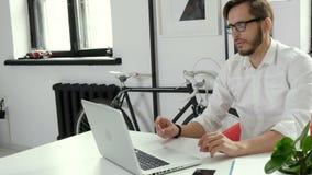 Młody człowiek pracuje w biurowym samotnym i ono uśmiecha się 4k zdjęcie wideo