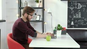 Młody człowiek pracuje w biurowym samotnym i ono uśmiecha się 20s 4k zbiory