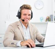 Młody człowiek pracuje w centrum telefonicznym Zdjęcie Royalty Free