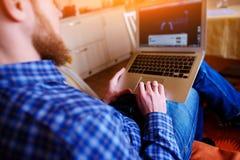 Młody człowiek pracuje z komputerem na plaży Przystojny mężczyzna worek zdjęcia stock