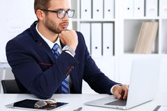 Młody człowiek pracuje z laptopem, mężczyzna ` s ręki na notatniku, biznesowa osoba przy miejscem pracy Zdjęcia Royalty Free