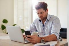 Młody człowiek pracuje z laptopem przy jego i telefon komórkowy stwarzamy ognisko domowe offic Zdjęcie Stock