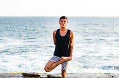 Młody człowiek praktyki joga na plaży z jasnym niebieskiego nieba tłem obraz stock