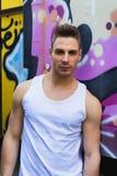 Młody człowiek przeciw jaskrawej barwionej graffiti ścianie obrazy stock