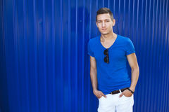 Młody człowiek przy błękitną ścianą fotografia stock