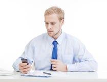 Młody człowiek przy biurem z telefon komórkowy zdjęcia stock