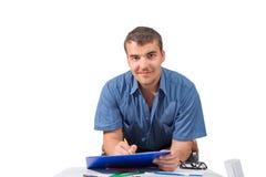 Młody człowiek przy stołem z falcówką w rękach na białym backgro Obraz Stock