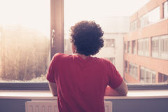Młody człowiek przyglądający out okno zdjęcie royalty free