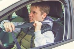 Młody człowiek przymocowywa Zbawczego pasek sejf kierowcy Obraz Stock