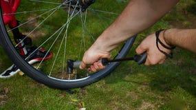 Młody człowiek ręki pompuje powietrze w rowerową oponę używać ręki pompę - wizerunek obraz royalty free