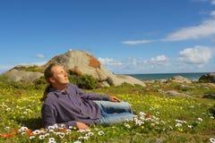 Młody człowiek relaksuje lying on the beach na kwiatu polu Zdjęcia Stock