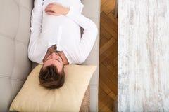 Młody człowiek relaksuje na kanapie Obrazy Royalty Free