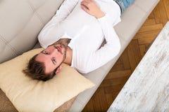 Młody człowiek relaksuje na kanapie obrazy stock