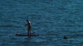Młody człowiek relaksuje na paddle desce na słonecznym dniu 4k, zwolnione tempo, telephoto obiektyw zdjęcie wideo