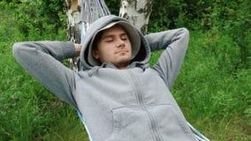 Młody człowiek relaksuje w hamaku zbiory