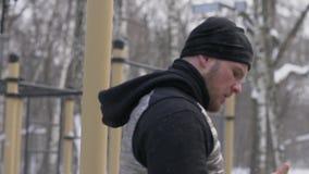 Młody człowiek robi ciągnienia up ćwiczeniu na zimy szkoleniu na sport ziemi zakończeniu up zbiory