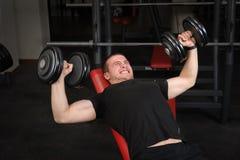 Młody człowiek robi Dumbbell pochylni ławki prasy treningowi w gym Zdjęcie Royalty Free