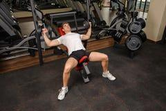 Młody człowiek robi Dumbbell pochylni ławki prasy treningowi w gym Zdjęcia Stock