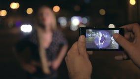 Młody człowiek robi fotografiom jego dziewczyna przy nocą zbiory wideo
