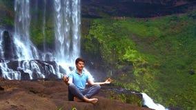Młody człowiek robi oddychania joga w padma asana przy siklawą zbiory