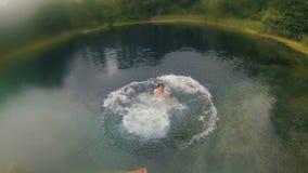 Młody człowiek robi tylnemu trzepnięciu od mola w jasnego błękitnego jezioro zdjęcie wideo