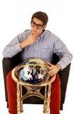 Młody człowiek rozpamiętywa życie z światową kulą ziemską w krześle Zdjęcie Royalty Free