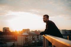 Młody człowiek rozpamiętywa na tarasie dach przeciw tłu pejzaż miejski przy zmierzchem zdjęcia stock