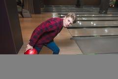 Młody człowiek rzuca kręgle piłkę Studenccy bawić się kręgle Obraz Stock