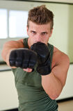 Młody człowiek rzuca poncz w kierunku kamery z bokser rękawiczkami Obrazy Royalty Free