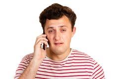 Młody człowiek słuchał złą wiadomość na telefonie i zaczyna płakać emocjonalny mężczyzna odizolowywający na białym tle zdjęcie royalty free