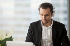 Młody człowiek słucha muzykę w biurze w hełmofonach fotografia stock