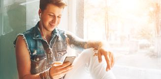 Młody człowiek słucha muzykę z hełmofonami i smartphone obsiadaniem dalej zdjęcie stock
