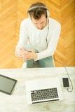 Młody człowiek słuchająca muzyka na jego laptopie fotografia stock