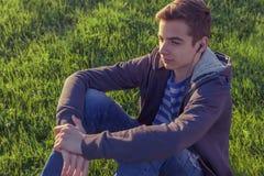 Młody człowiek słuchająca muzyka od mądrze telefonu na trawie w parku Zdjęcia Stock