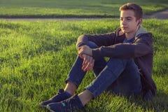 Młody człowiek słuchająca muzyka od mądrze telefonu na trawie w parku Obrazy Royalty Free