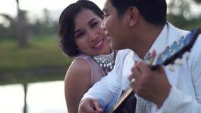 Młody człowiek serenad sympatia z gitary kobiety spojrzeniami przy chłopakiem zdjęcie wideo
