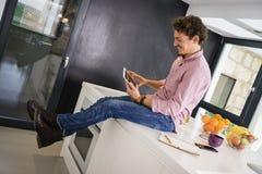 Młody człowiek, siedzący na kuchennym kontuarze, ogląda pastylkę zdjęcie royalty free