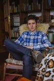 Młody człowiek siedzi dalej z szkocka krata cajgami i koszula zdjęcia royalty free