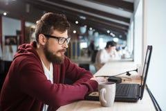 Młody człowiek siedzi laptop i używa w szkłach fotografia royalty free
