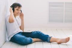 Młody człowiek siedzi na słuchaniu i podłoga muzyka fotografia royalty free