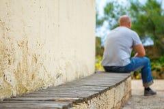 Młody człowiek siedzi samotnie na parkowej ławce fotografia royalty free