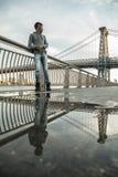 Młody człowiek siedzi widok NYC ` s Williamsburg Brid i podziwia Obrazy Stock